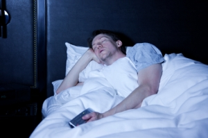 Man in bed with TV remote